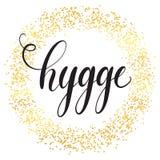 Hygge在金黄圈子微粒背景的手字法 属于片刻并且享受简单的事概念 免版税库存图片