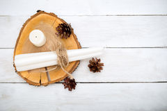 hygge Οι κώνοι και τα κεριά βρίσκονται σε μια ξύλινη στάση σε ένα λευκό ξύλινο Στοκ Φωτογραφίες