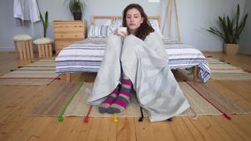 Hygge concept - beautiful attractive girl sitting, wrapped in a cozy blanket on the floor in her bedroom and resting. 4k stock video footage