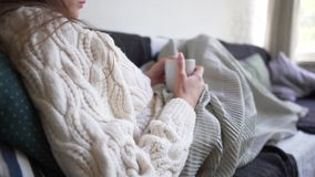 Hygge concept - a woman in a white sweater holds a hot cup of fresh coffee in her hands. Girl resting on a couch. Recline on pillows and hiding in a blanket 4k stock video