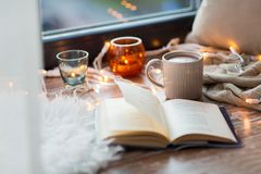 Book and coffee or hot cchocolate on window sill. Hygge and cozy home concept - book, cup of coffee or hot cchocolate and candles with garland on window sill royalty free stock photo