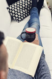 Hygge, danish word for comfort or enjoy. Closeup of a young man reading a book with a cup of coffee in his hand with the text hygge, a danish and norwegian word royalty free stock photo