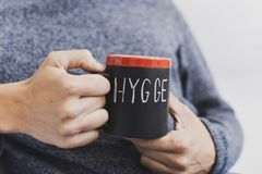 Hygge, danish word for comfort or enjoy. Closeup of a young man sitting comfortably with a cup of coffee in his hand with the word hygge written in it, a danish stock images