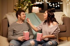 Happy couple eating popcorn at home. Hygge, leisure and people concept - happy couple eating popcorn at home stock photos