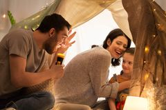 Father telling scary stories to his daughter. Hygge and people concept - father with torch light telling scary stories to his daughter and wife, family having Stock Photos