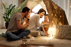 Father telling scary stories to his daughter. Hygge and people concept - father with torch light telling scary stories to his daughter and wife, family having stock photography