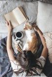 Hygge pojęcie z kotem, książką i kawą w łóżku, zdjęcie royalty free