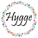 Hygge sign symbolizing Danish Life style surrounded by colorful spring inspired circle surrounded by flowers, leaves, butterflies. Bees, clovers, hearts Stock Image