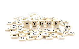 HYGGE  spelt on word tiles. On a white background, Hygge is a Danish and Norwegian word which can be described as a quality of cosiness and comfortable Stock Photos