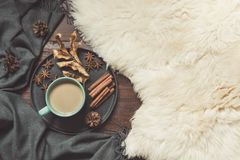 Hygge still life with hot cup of black coffee, anise, warm scarf on furskin and wooden board. Copy space. Top view. Hygge still life with hot cup of black stock photos