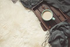 Hygge still life with hot cup of black coffee, anise, warm scarf on furskin and wooden board. Copy space. Top view. Hygge still life with hot cup of black royalty free stock photo