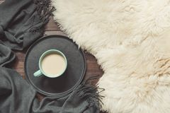 Hygge still life with hot cup of black coffee, warm scarf on furskin and wooden board. View from above. Hygge still life with hot cup of black coffee, warm scarf royalty free stock photo