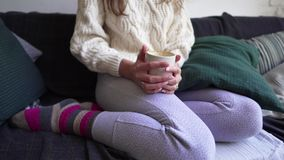 Hygge - a young woman in warm multi-colored socks, pajama pants and a woolen sweater sits on a soft sofa with a mug of. Hot coffee 4k stock footage