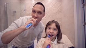 Hygiène buccale, papa joyeux avec la fille avec les dents de brossage de brosse à dents devant le miroir banque de vidéos