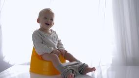 Hygiène d'enfants, nourrisson heureux s'asseyant sur le pot et sourires dans la chambre lumineuse clips vidéos
