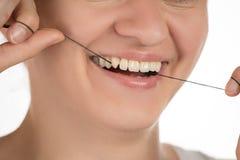 Hygiène de la cavité buccale La jeune fille nettoie des dents avec la soie, Photo stock