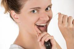 Hygiène de la cavité buccale La jeune fille nettoie des dents avec la soie, Images stock