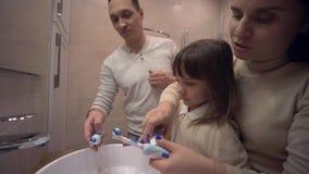Hygiène de matin, jeune mère et fille d'enfant d'enseignement de papa avec des dents de brosse de brosse à dents devant le miroir clips vidéos