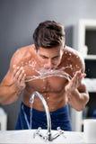 Hygiène de matin, visage de lavage d'homme photographie stock libre de droits