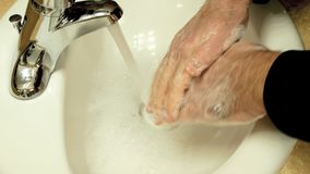 Hygiene. Closeup of a man cleaning his hands by washing them with soap and water. stock footage