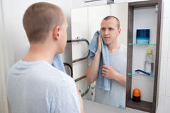 Hygiene concept - handsome man looking at mirror after shaving i Stock Image