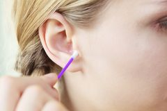 Woman cleaning ear with cotton swabs closeup. Hygiene concept. Young woman cleaning ear with cotton swabs closeup royalty free stock photos