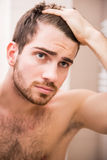 Hygiene. Handsome man is checking hairline while looking at the mirror Stock Image