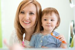 Hygiene. Happy mother and child brushing teeth Stock Image