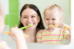 Hygiene. Happy mother and child brushing teeth Royalty Free Stock Image