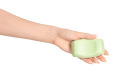 Hygiene and health care topic: a woman's hand holding a green bar of soap isolated on white background in studio Royalty Free Stock Photography
