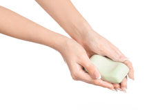 Hygiene and health care topic: a woman's hand holding a green bar of soap isolated on white background in studio Royalty Free Stock Photos