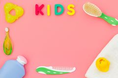 Hygiene items for the child. Bath accessories with yellow rubber duck on pink background top view copy space frame. Word royalty free stock images