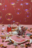 Hygiene items in red and bubbles. Some hygiene items in red and some soap bubbles on a red bamboo mat Stock Photo
