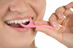 Hygiene of the oral cavity. Young girl cleans teeth with floss,. Smiling and showing okay sign on white background stock images