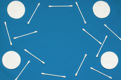Hygiene products: round white cotton pads and cotton swabs are on colored background. Top view, flat lay stock images