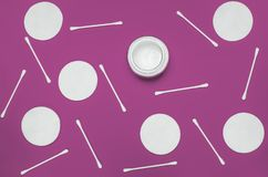 Hygiene products: round white cotton pads and cotton swabs are on colored background. Top view, flat lay royalty free stock photo