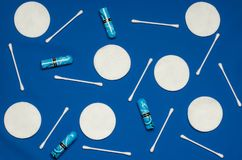 Hygiene products: round white cotton pads and cotton swabs are on colored background. Top view, flat lay stock image