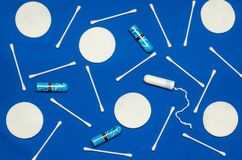 Hygiene products: round white cotton pads and cotton swabs are on colored background. Top view, flat lay stock photography