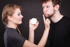 Female beautician apply cream on male mouth. Hygiene and skincare concept. Young blonde female beautician cosmetician apply cream on male mouth lips. Woman and Royalty Free Stock Images