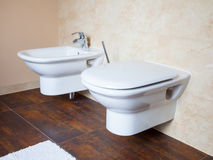 Hygiene. White porcelain bidet and toilet. Interior of bathroom. Hygiene and physiological needs. Closeup of white porcelain bidet and toilet wc. Interior of Royalty Free Stock Images