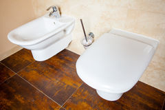 Hygiene. White porcelain bidet and toilet. Interior of bathroom. Stock Photo
