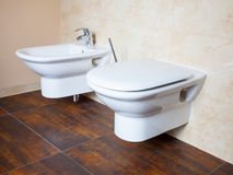 Hygiene. White porcelain bidet and toilet. Interior of bathroom. Stock Photography