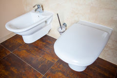 Hygiene. White porcelain bidet and toilet. Interior of bathroom. Royalty Free Stock Photography