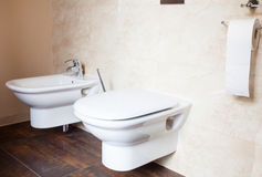 Hygiene. White porcelain bidet and toilet. Interior of bathroom. royalty free stock image
