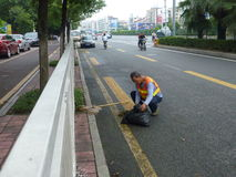 Hygienearbeitskräfte im Abbau des Straßenrands säubert Stockbild