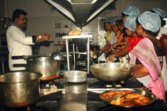 Hygienic Cooking. A group of Indian village women are practicing as per instruction in a training program of hygienic and healthy use of kitchen during cooking royalty free stock image