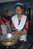 Hygienic Cooking. An Indian village women are practicing as per instruction in a training program of hygienic and healthy use of kitchen during cooking. There royalty free stock photos