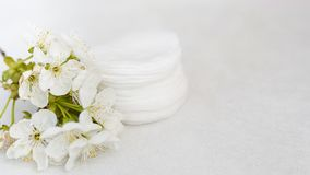 Hygienic disposable product cosmetic pads and flower on white towel background with copy space . skin body care concept.  royalty free stock photos
