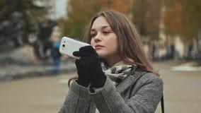 Hygienischer Lippenstift des jungen schönen Mädchenlippenstifts auf einer Stadtstraße Herbst kalt stock video footage