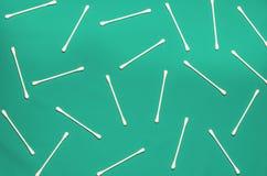 Hygienprodukter: är vita bomullsblock för rundan och bomullsbomullstoppar på kulör bakgrund royaltyfria foton